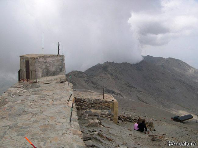 Caseta en la cumbre del Veleta, al fondo, entre nubes, los Tajos de la Virgen y del Nevero