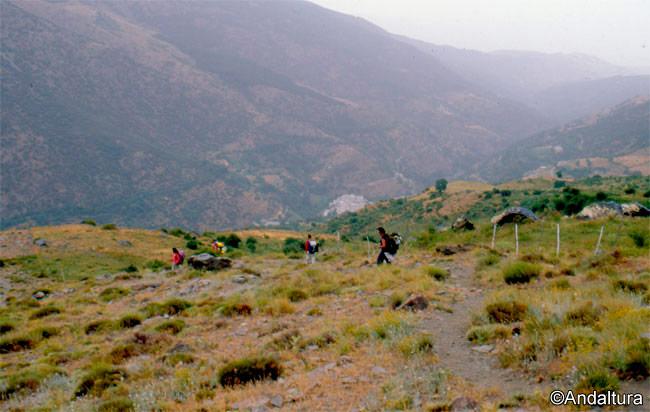 Senderistas descendiendo a Trevélez, al fondo